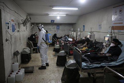 Ein Mitglied des syrischen Zivilschutzes versprüht Desinfektionsmittel. Foto:Anas Alkharboutli/dpa