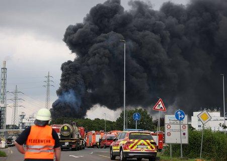 Einsatzfahrzeuge der Feuerwehr stehen unweit einer Zufahrt zum Chempark, über dem eine gewaltige dunkle Rauchwolke aufsteigt. Foto: Oliver Berg/dpa