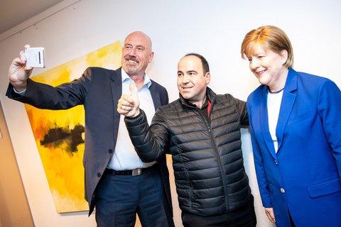 Merkel-Fan Alexis Vaiou (M) und Carsten Meyer-Heder (l), Landesvorsitzender der CDU Bremen, machen ein Selfie mit der lebensgroßen Wachsfigur von Bundeskanzlerin A. Merkel. Foto:Sina Schuldt/dpa
